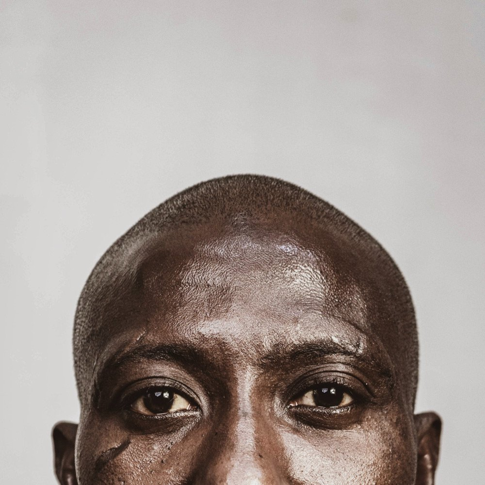 An image of a black man with a shaved head, looking directly at the camera.