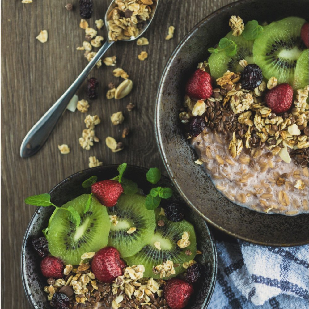 An image of two bowls of granola with fresh and dried fruits including kiwi and raspberries, plus seeds
