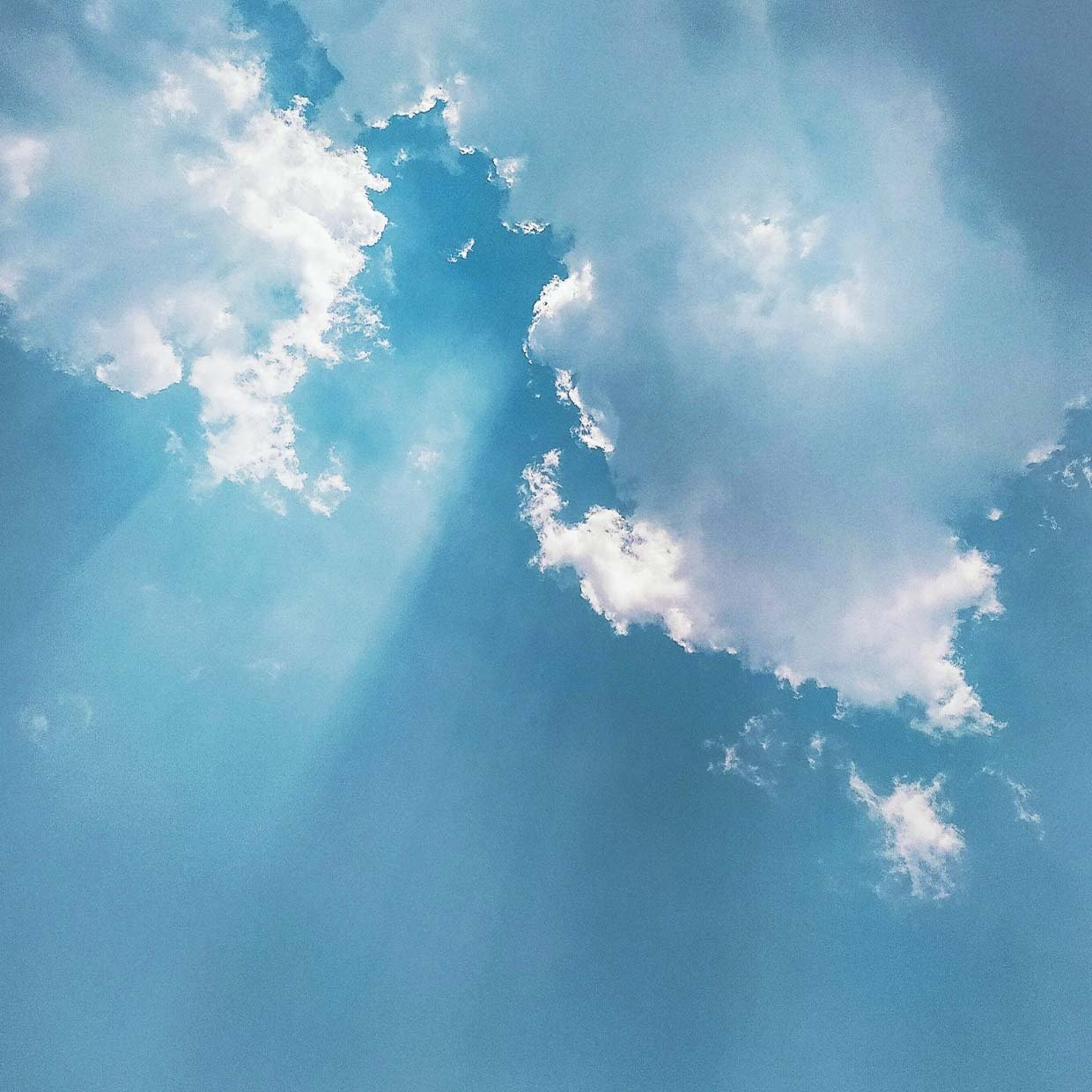 An image of the sky with sunlight coming through the clouds