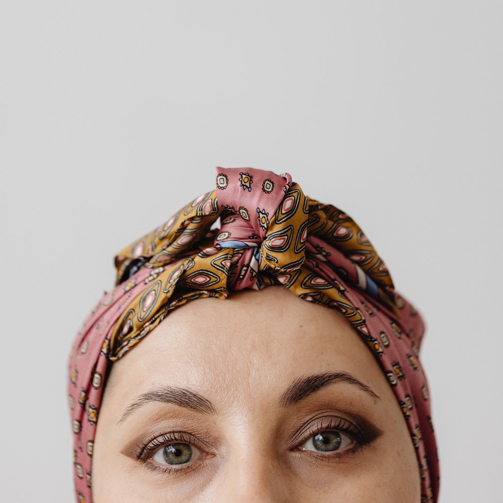 An image of a white woman wearing a headscarf, looking directly at the camera.