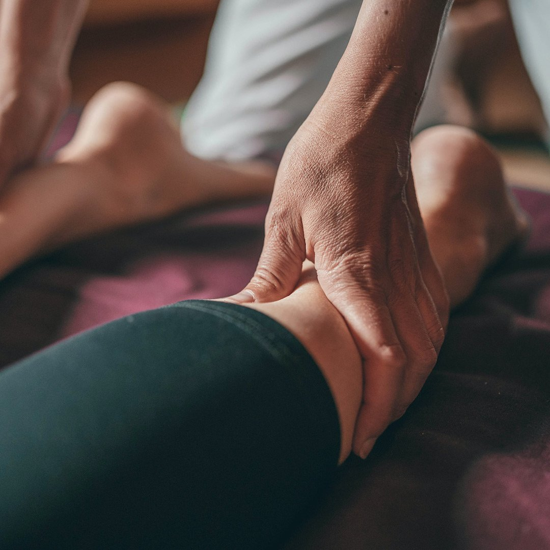 An image of someone receiving gentle massage on the backs of their legs.